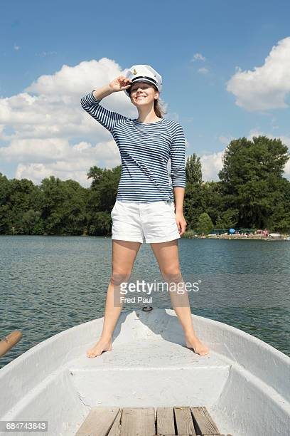 young woman standing in a boat - セーラーハット ストックフォトと画像