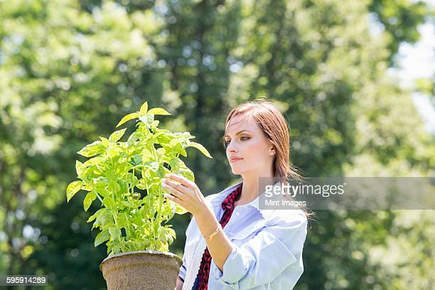 A young woman standing in a garden tending a plant in a pot.