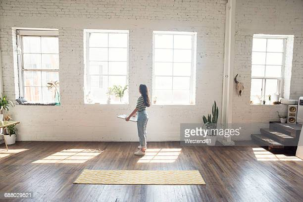 young woman standing in a loft holding picture frame - loft stock photos and pictures