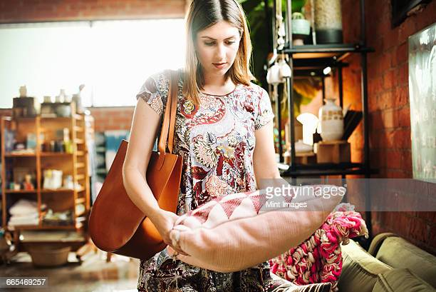 young woman standing in a shop, holding a cushion. - cushion stock photos and pictures
