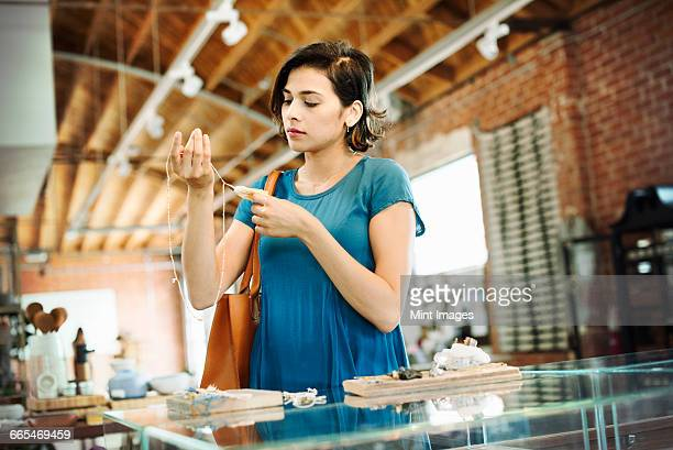young woman standing in a shop, looking at a necklace. - ギフトショップ ストックフォトと画像