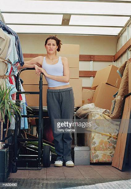 Young woman standing in back of moving truck, portrait