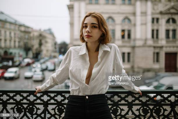 young woman standing in balcony - woman flat chest stock photos and pictures