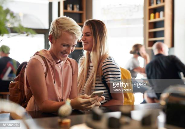 young woman standing in café and laughing while looking at phone - differential focus stock pictures, royalty-free photos & images