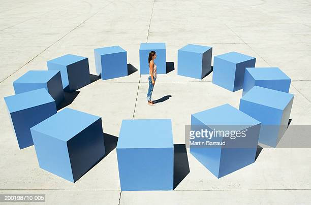 Young woman standing in circle arrangement of large blue cubes