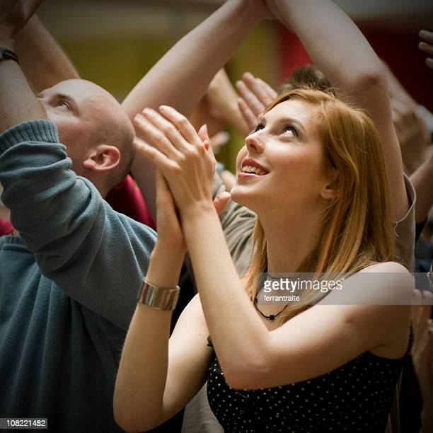 Young Woman Standing in Crowd and Clapping