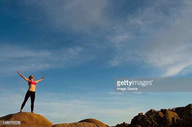 young woman standing in desert with arms open - open source photos et images de collection