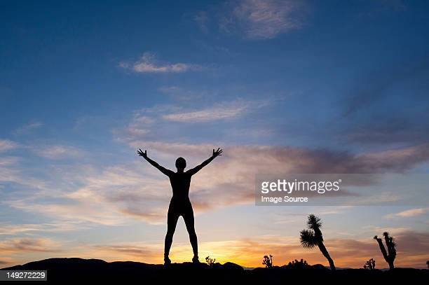 young woman standing in desert with arms open, silhouette - open source photos et images de collection