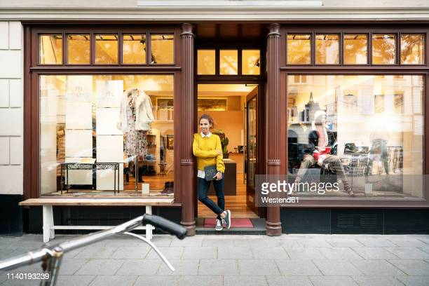young woman standing in door of a fashion store, holding laptop - shop window stock pictures, royalty-free photos & images