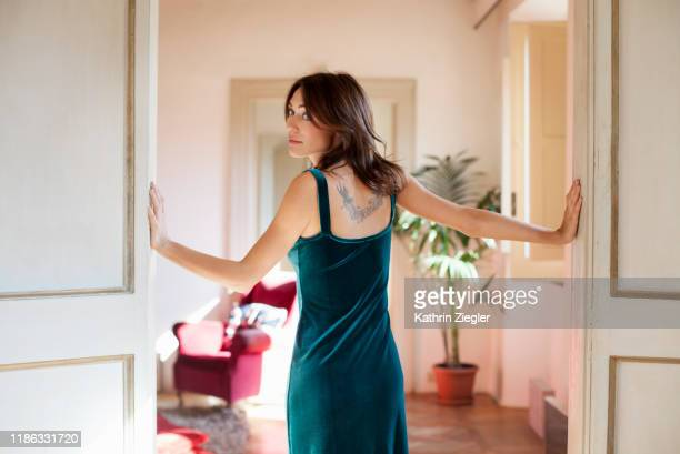 young woman standing in doorway of elegant apartment, looking over her shoulder - kleid stock-fotos und bilder