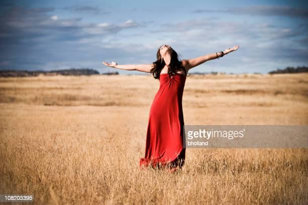 young woman standing in field and throwing arms up - bruin haar stockfoto's en -beelden