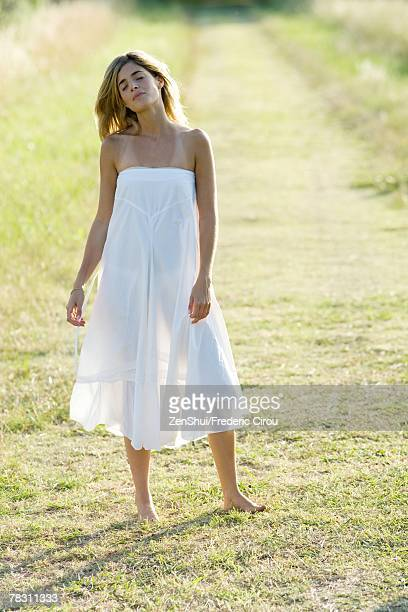 young woman standing in field, eyes closed, full length - women in see through dresses stock photos and pictures