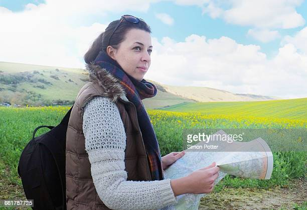 Young woman standing in field, holding map