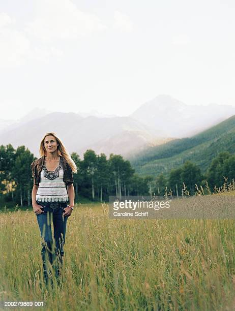 young woman standing in field of tall grass, hands in pockets, smiling - schiff stock photos and pictures