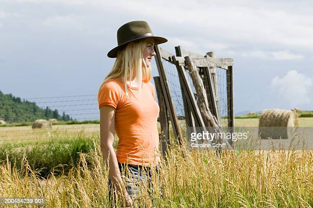 young woman standing in field, side view - schiff stock photos and pictures