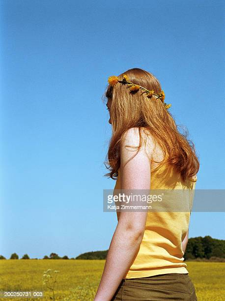 Young woman standing in field wearing daisy chain on head