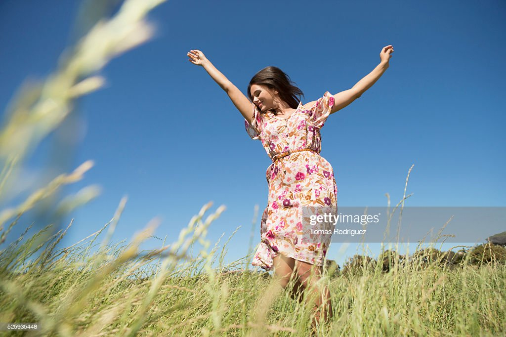 Young woman standing in field with arms raised : Foto stock