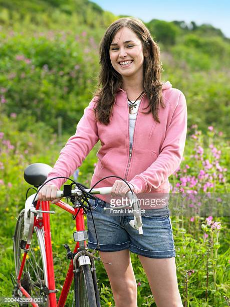 Young woman standing in field with bicycle, smiling, portrait