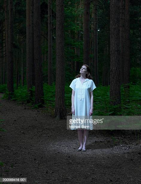 Young woman standing in forest, looking up