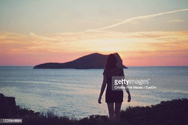 young woman standing in front a small island at the sunset hour - islas baleares fotografías e imágenes de stock