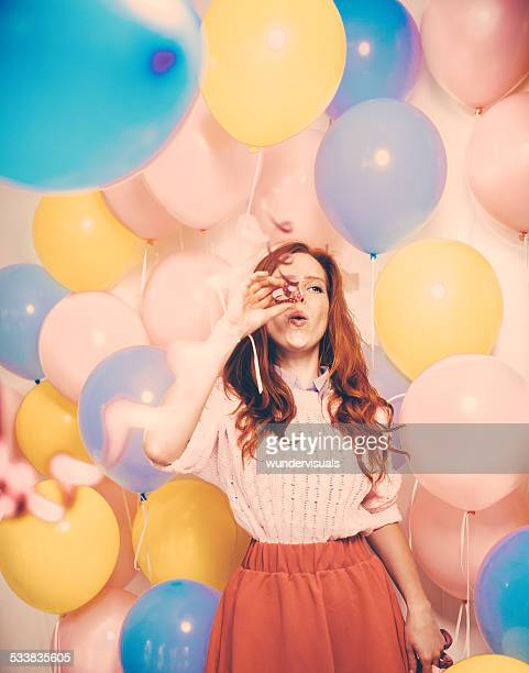 young woman standing in front of a balloon wall - streamer stock photos and pictures