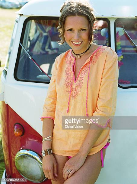 Young woman standing in front of camper van, smiling, portrait