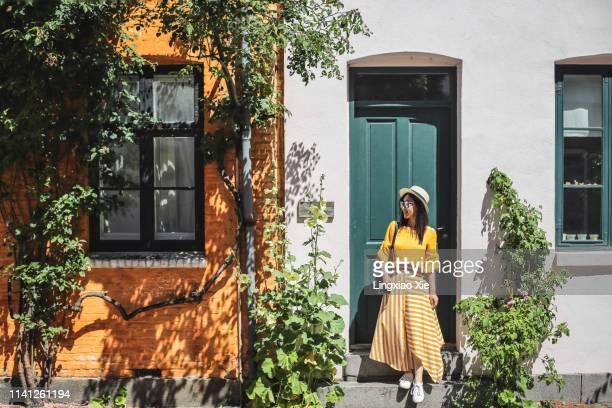 young woman standing in front of colorful buildings in copenhagen, denmark - flerfärgad klänning bildbanksfoton och bilder