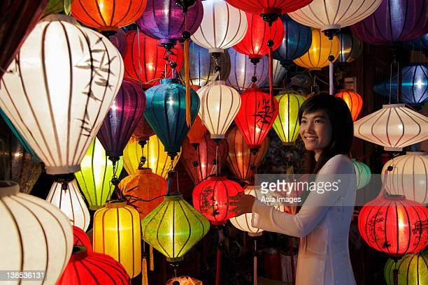 Young woman standing in front of colorful, hanging lanterns
