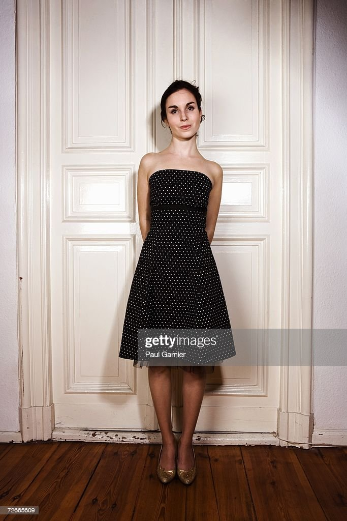 Young woman standing in front of double door wearing polka dot tube dress : Stock Photo