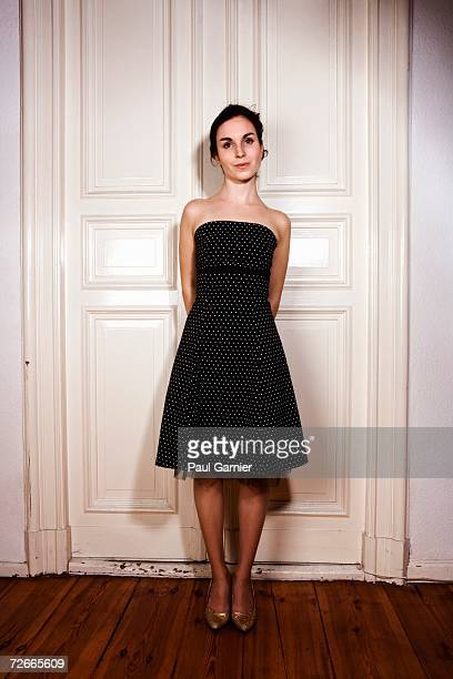young woman standing in front of double door wearing polka dot tube dress - strapless dress stock pictures, royalty-free photos & images