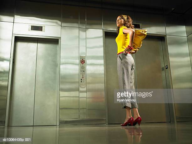 Young woman standing in front of elevator, checking reflection