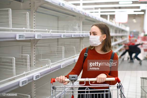 young woman standing in front of empty shelf in a supermarket - sold out stock pictures, royalty-free photos & images