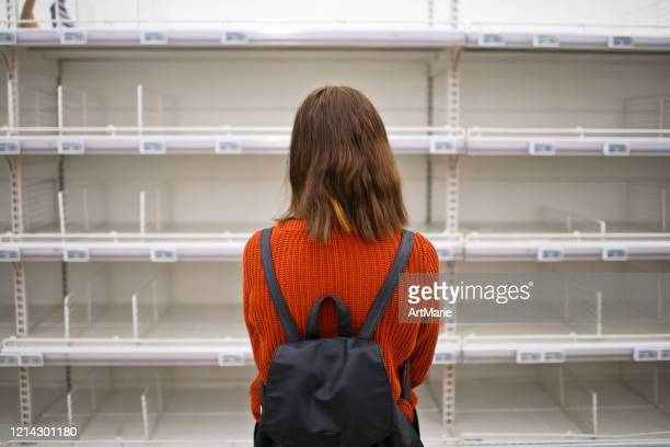 young woman standing in front of empty shelf in a supermarket - sparse stock pictures, royalty-free photos & images