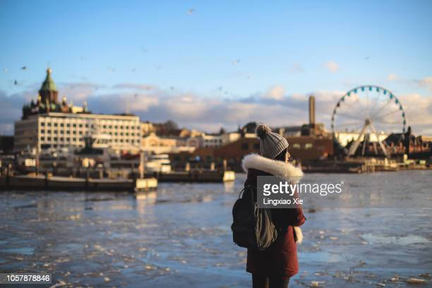 young woman standing in front of frozen ice with south harbour urban skyline, helsinki, finland - helsinki stockfoto's en -beelden