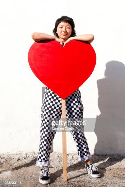 young woman standing in front of giant heart on stick - i love you stock pictures, royalty-free photos & images