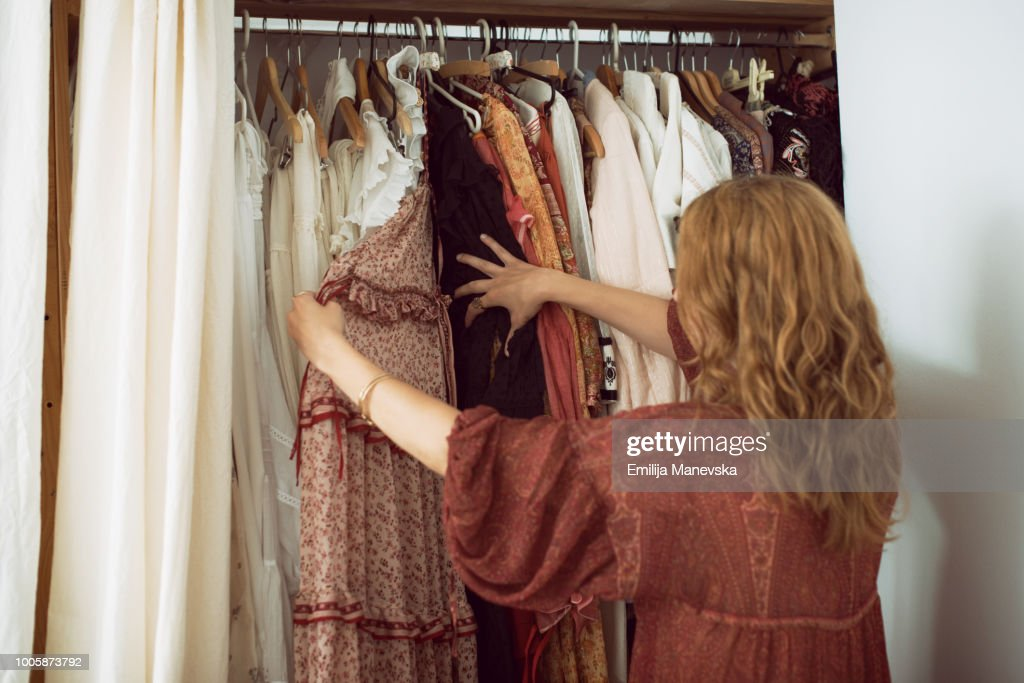 Young woman standing in front of her closet choosing something to wear : Foto de stock