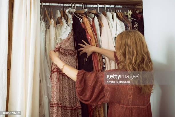 young woman standing in front of her closet choosing something to wear - kast stockfoto's en -beelden