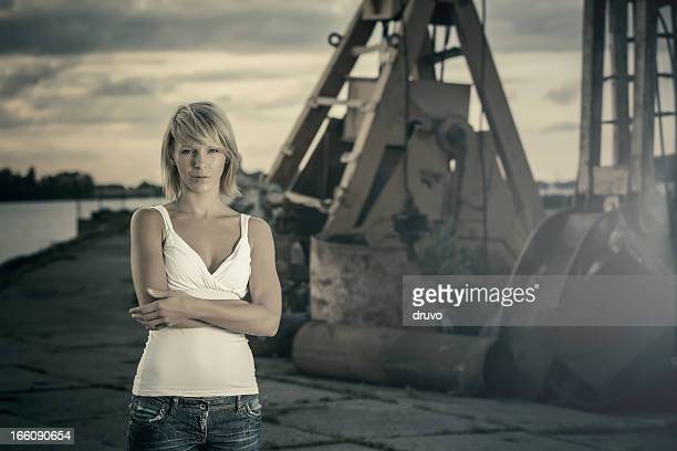 Young woman standing in front of industrial site
