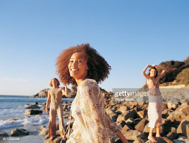 young woman standing in front of man and woman on the beach - travel14 stock pictures, royalty-free photos & images