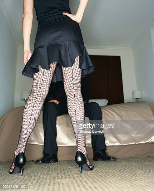 young woman standing in front of man on bed, rear view, low section - seamed stockings stock photos and pictures