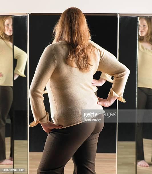Junge Frau stehend vor Spiegel, Hände auf
