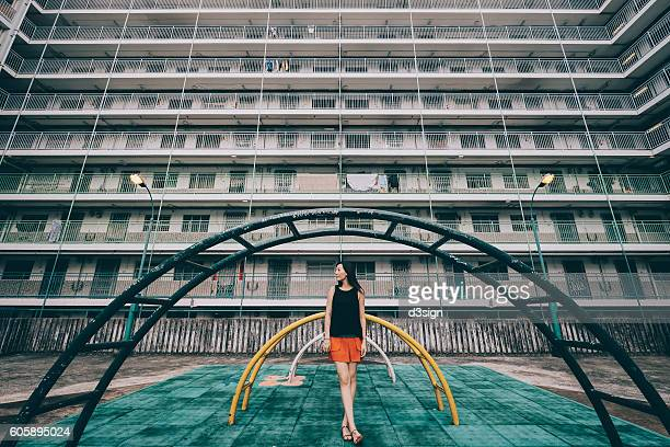 Young woman standing in front of old styled playground in a public housing estates in Hong Kong.