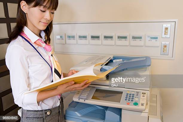 Young Woman Standing In Front Of Photocopier Reading Document