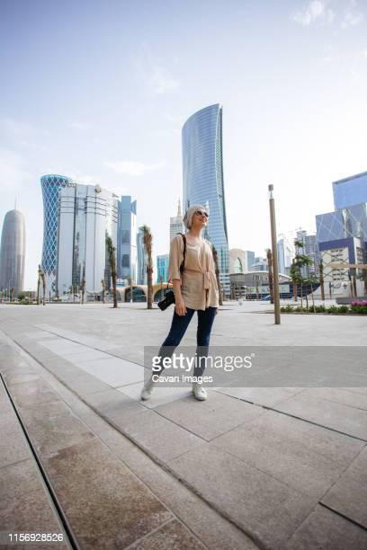 young woman standing in front of skyscrapers in doha - doha stock pictures, royalty-free photos & images
