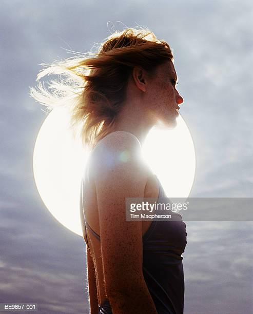 young woman standing in front of sun, backlit - espiritualidad fotografías e imágenes de stock