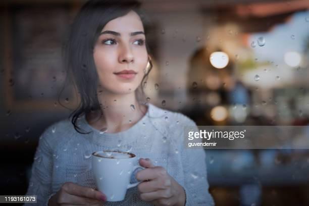 jeune femme restant devant la fenêtre et appréciant une tasse de café à la maison un jour pluvieux - front view photos et images de collection