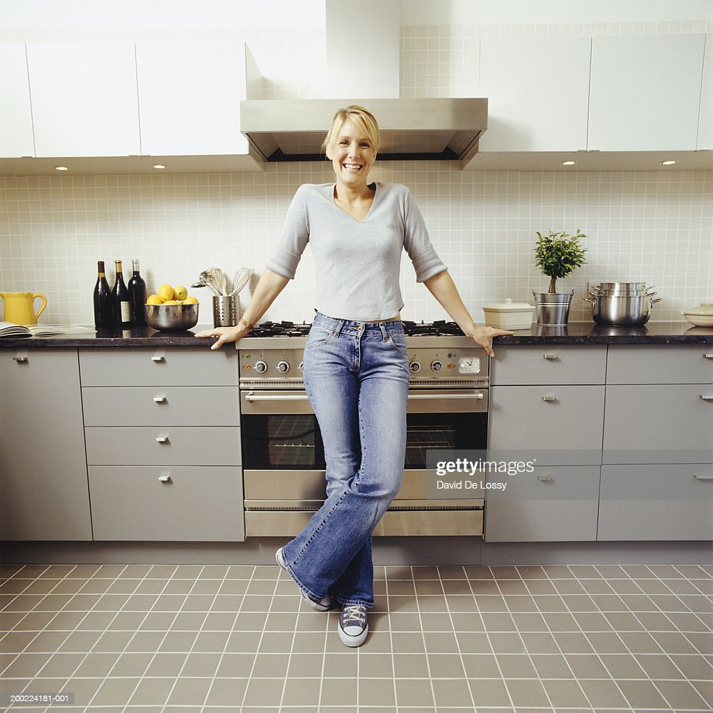 Women Kitchen: Young Woman Standing In Kitchen Portrait High-Res Stock