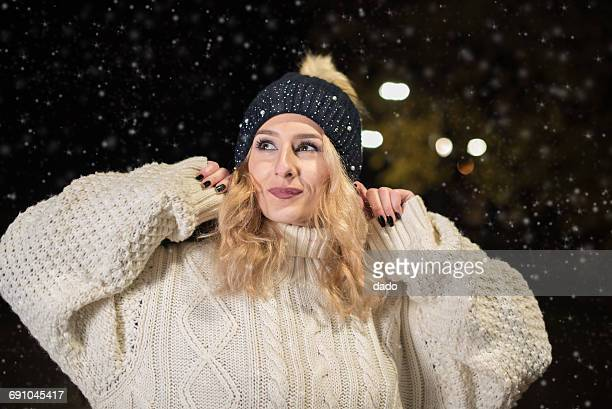 Young woman standing in knitted jumper in snow