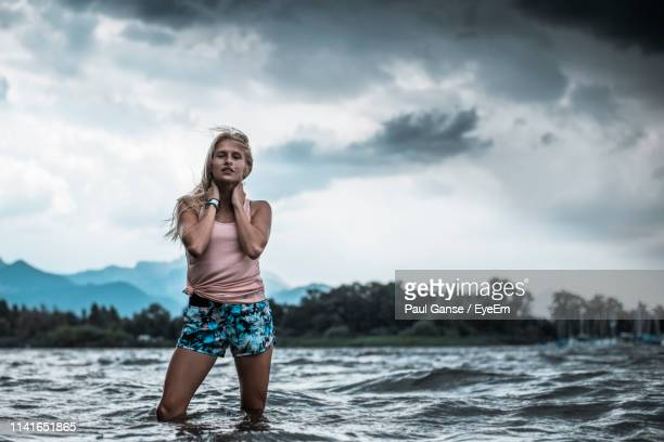 young woman standing in lake against cloudy sky - ウォーターフロント ストックフォトと画像