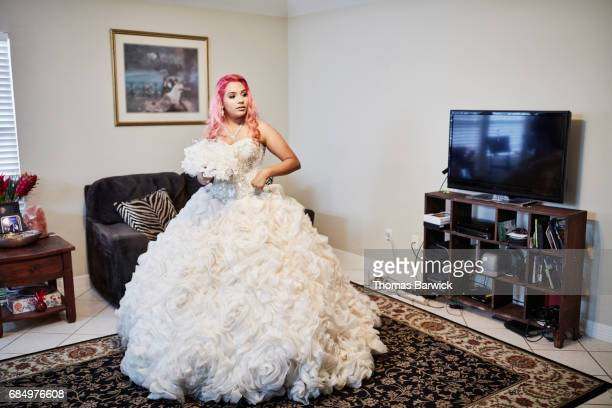 Young woman standing in living room dress in quinceanera gown
